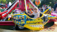Sophie riding on a yellow Minions aeroplane at the funfair
