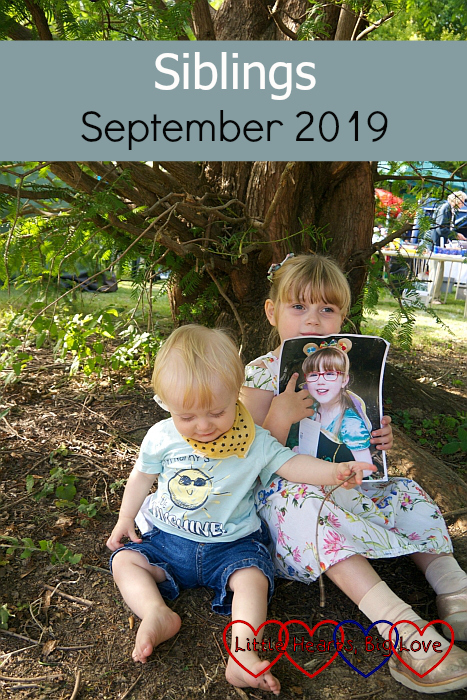 "Sophie and Thomas sitting under a tree at Pinner Village Show. Sophie is holding a picture of Jessica. ""Siblings - September 2019"""