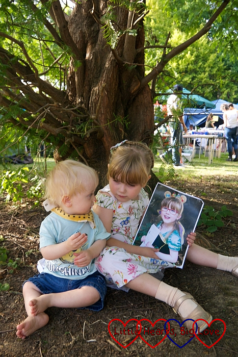 Sophie and Thomas sitting under a tree at Pinner Village Show. Sophie is holding a picture of Jessica