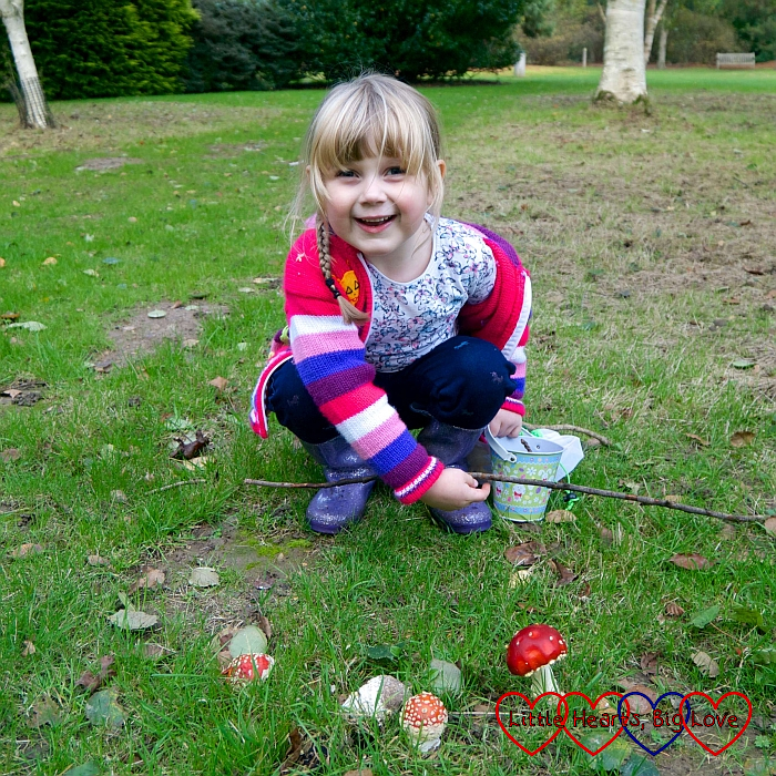 Sophie crouching down behind a couple of fly agaric toadstools
