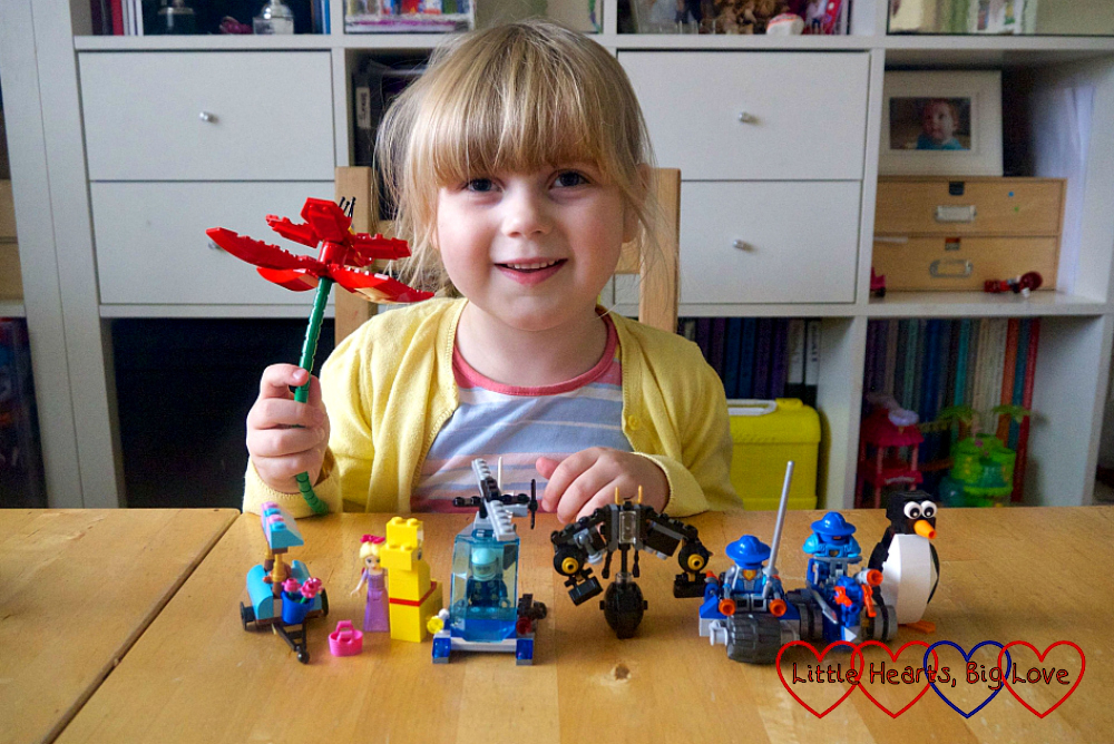 Sophie holding a brick flower with a selection of brick models (car, giraffe, helicopter, robot and penguin) in front of her