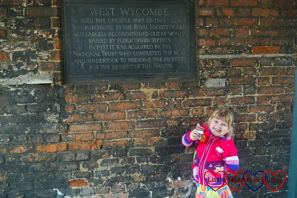 Sophie standing in front of a sign saying about how the National Trust purchased West Wycombe village