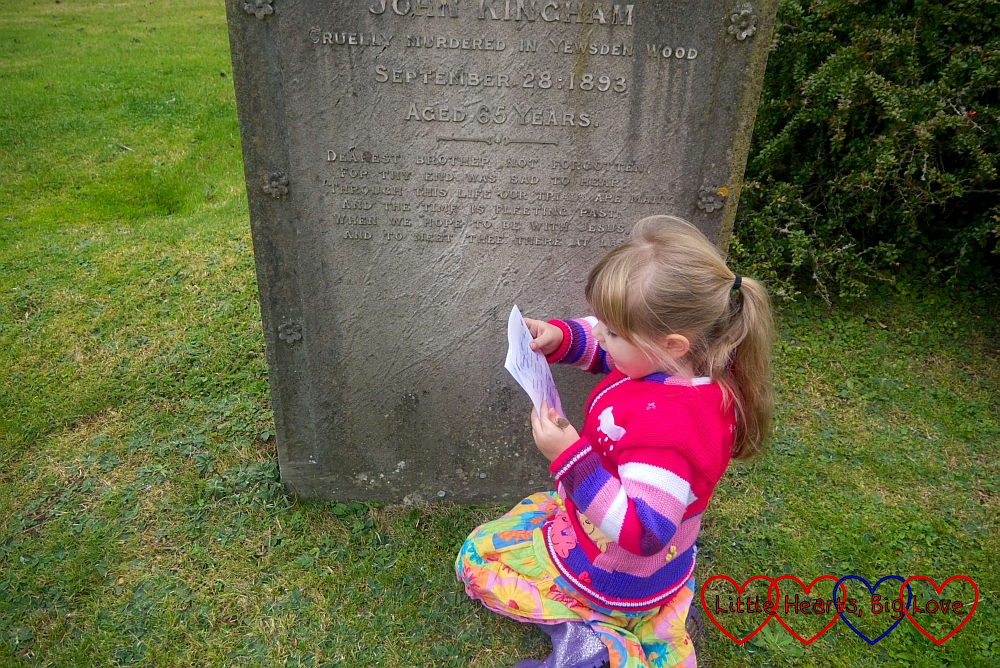 Sophie in front of a gravestone in Bledlow Ridge churchyard, ticking off an answer on her trail sheet