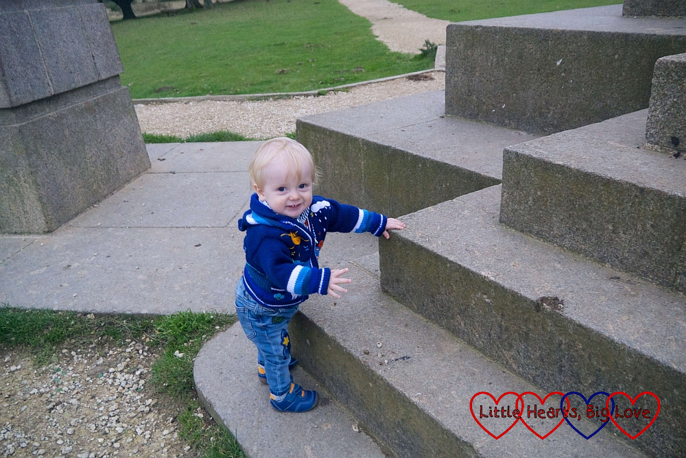 Thomas standing up holding on to the steps of the Boer War Monument