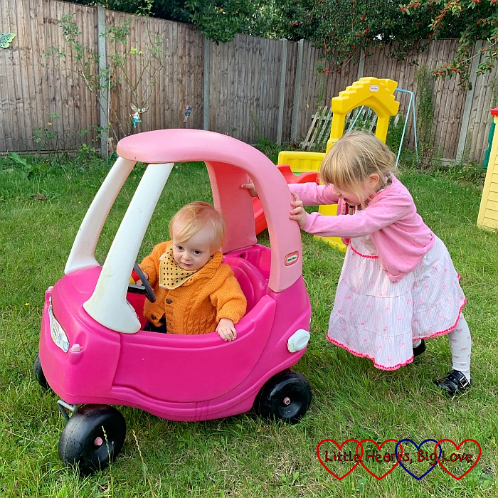 Sophie pushing Thomas in a Little Tikes car in the garden