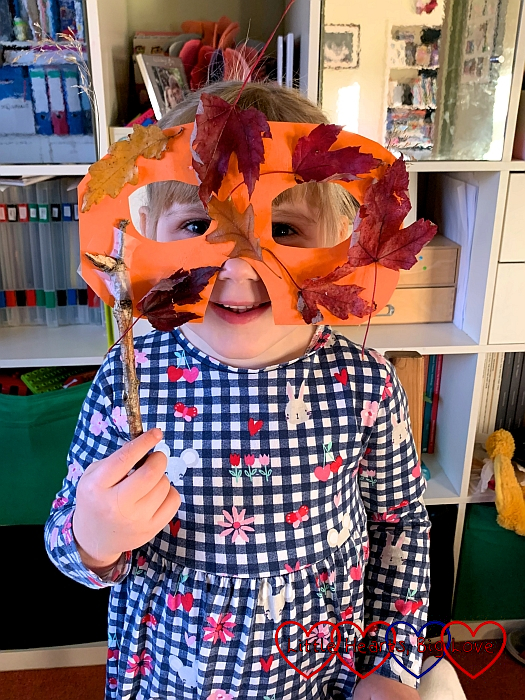 Sophie with her autumn mask covered in autumn leaves