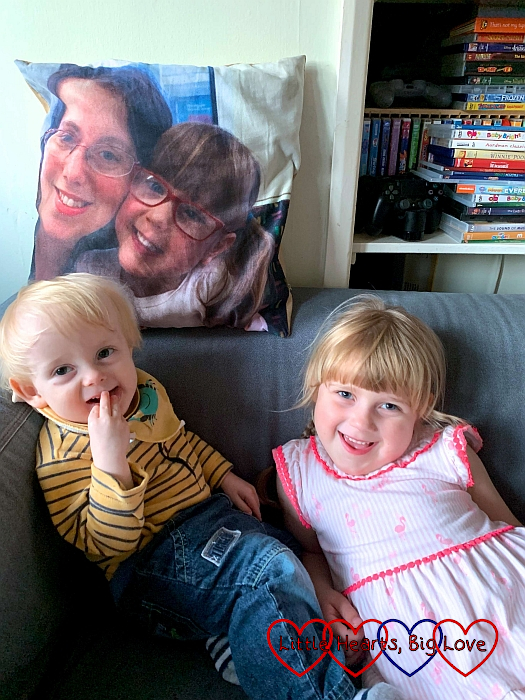 Thomas and Sophie sitting on the sofa in front of Jessica's photo cushion