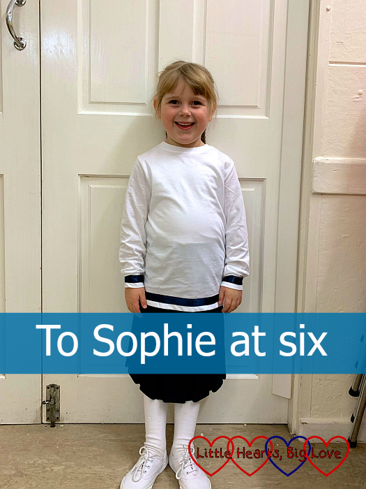 "Sophie in front of a white door wearing her sailor outfit for The Sound of Music - ""To Sophie at six"""