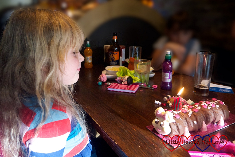 Sophie blowing out the candle on her Connie the Caterpillar birthday cake
