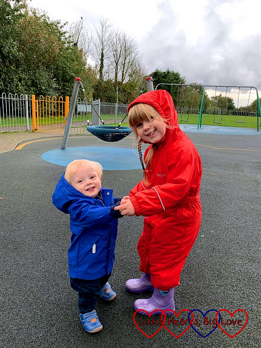 Sophie holding Thomas's hands at the park