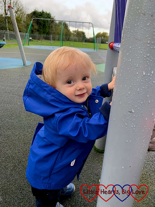 Thomas holding on to the side of the climbing frame
