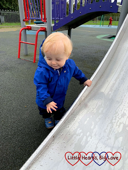 Thomas walking while holding on to the slide at the park