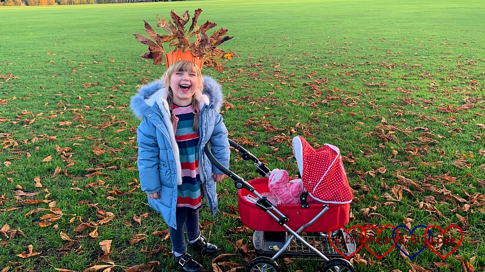 Sophie with her doll's pram, wearing her autumn crown