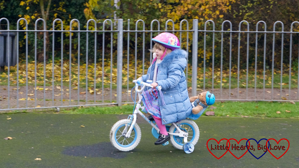 Sophie riding her bike around the park with Walter strapped into the seat behind her