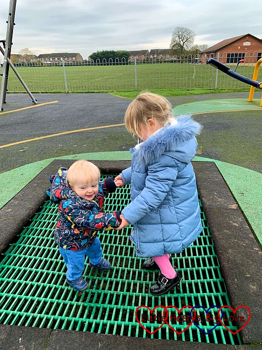 Sophie holding Thomas's hands as they bounce on the trampoline at the park