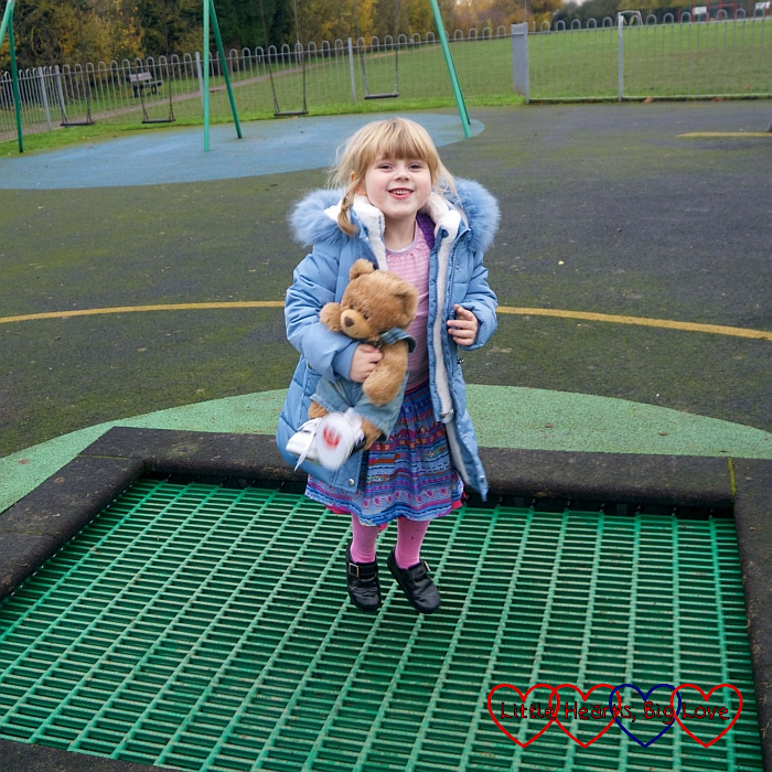 Sophie holding Walter the bear while bouncing on the trampoline at the park