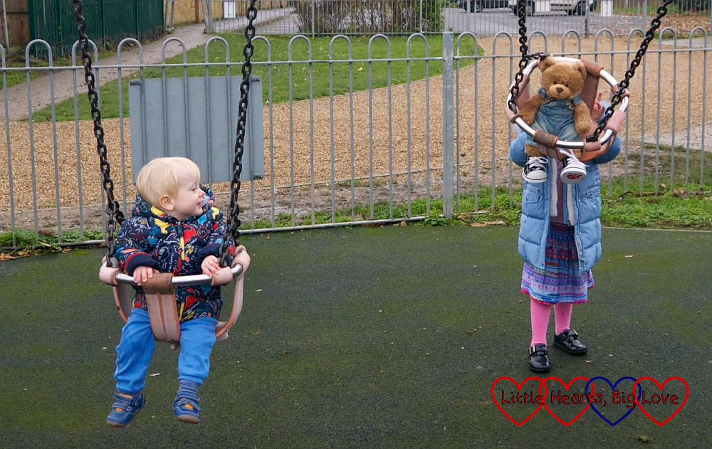 Thomas sitting in the baby swing with Sophie pushing Walter in the swing next to him