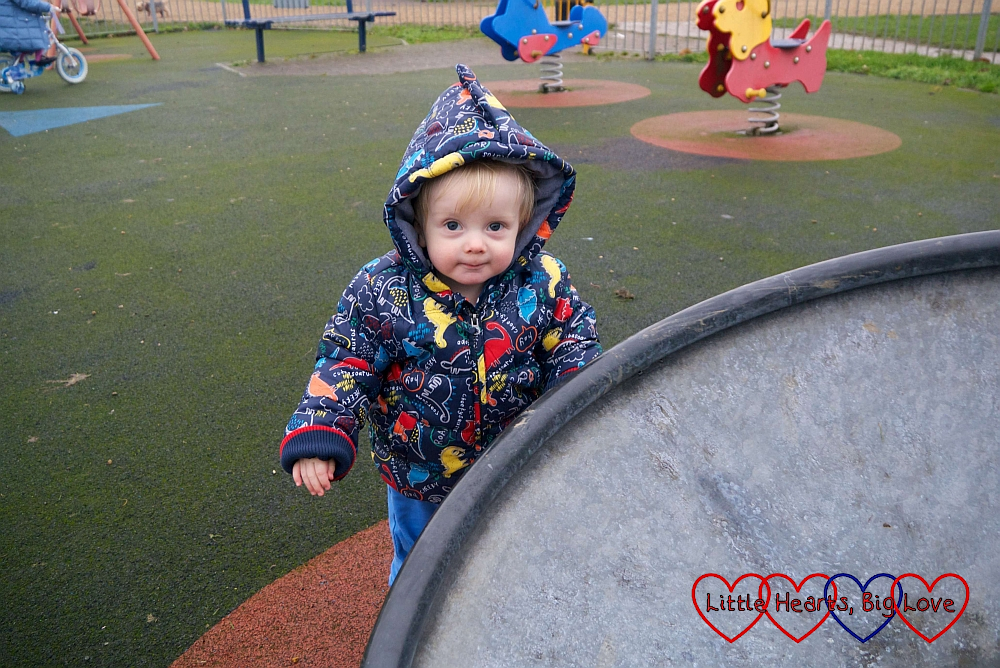 Thomas standing next to the spinning saucer at the park