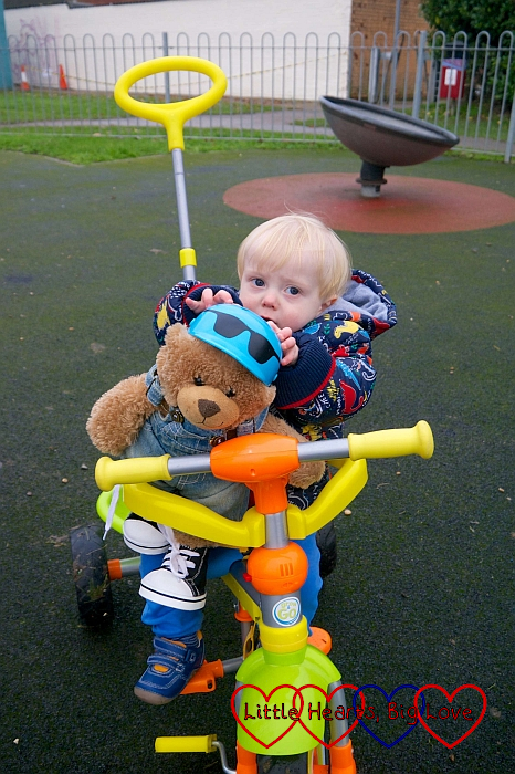 Thomas sitting in his trike, holding Walter the bear