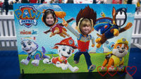 Sophie and her friend popping their heads through the holes in the PAW Patrol mosaic brick board.