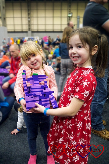 Sophie and her friend holding their creation from the purple brick pit