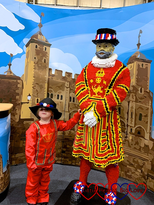 Sophie wearing a Beefeater costume standing next to a brick model of a Beefeater with a Tower of London backdrop.