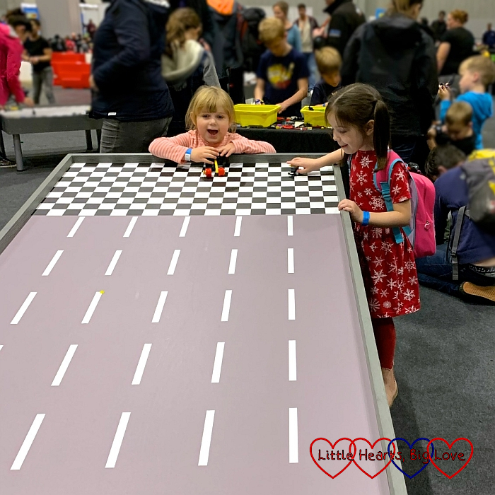 Sophie and her friend racing a car down one of the racing ramps