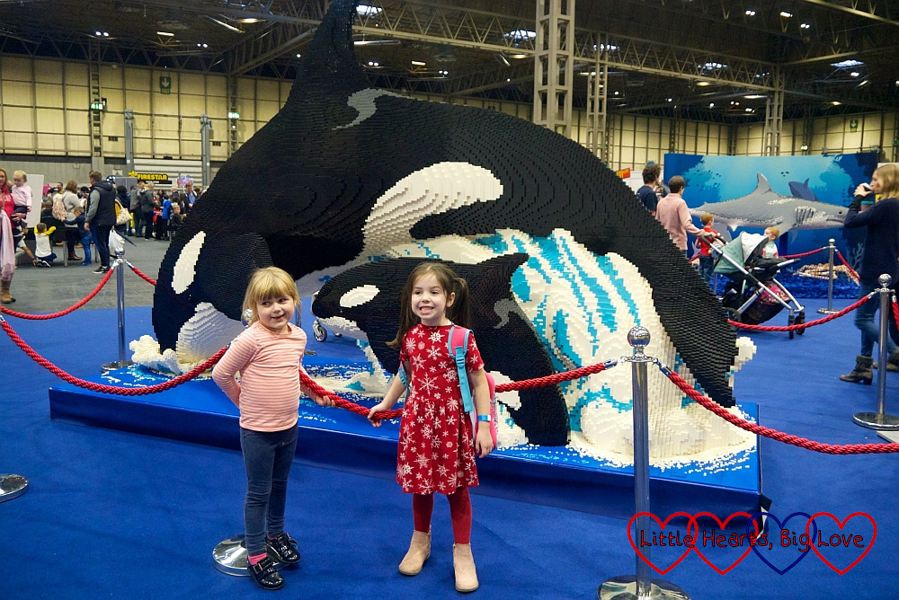Sophie and her friend in front of the brick model of a killer whale and her baby