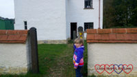 Sophie looking at the 'listen' and 'feel' signs outside the Haddenham Croft Cottage