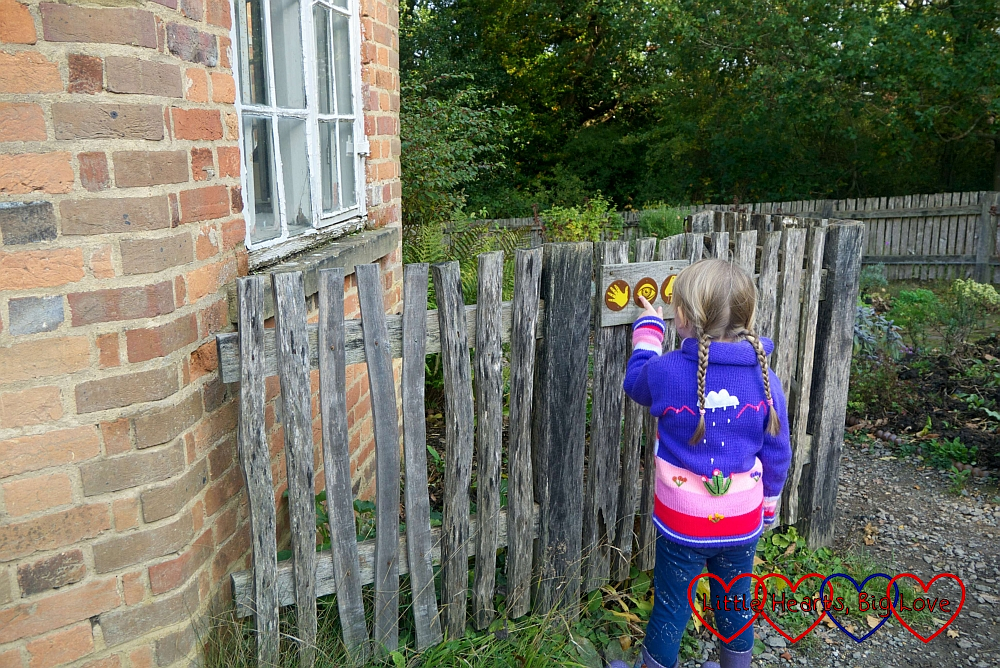 """Sophie looking at the """"feel"""", """"see"""" and """"smell"""" signs outside the High Wycombe Toll House"""