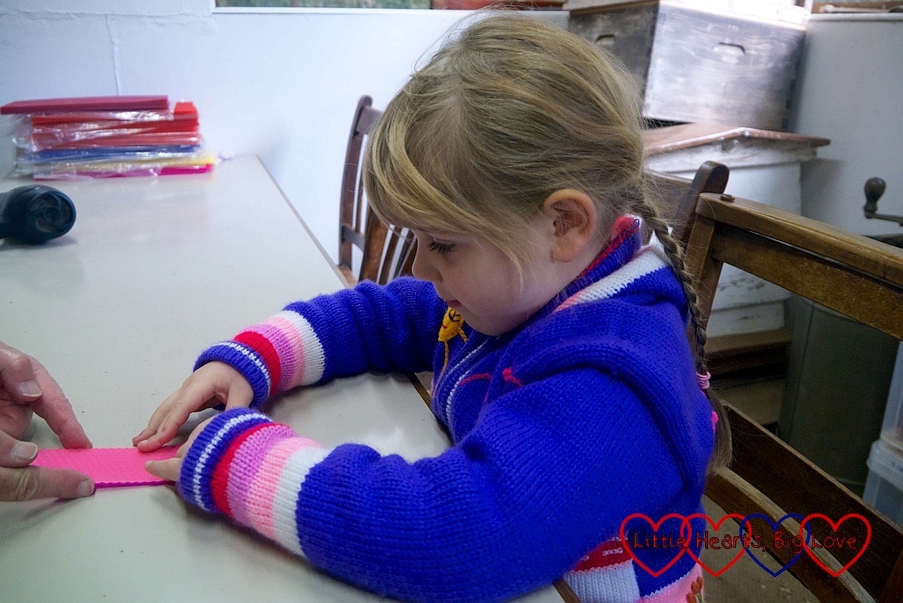 Sophie making a beeswax candle by rolling pink and purple wax