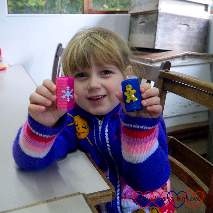 Sophie holding up two finished candles – a pink and purple one with a snowflake motif and a blue one with a gingerbread man motif