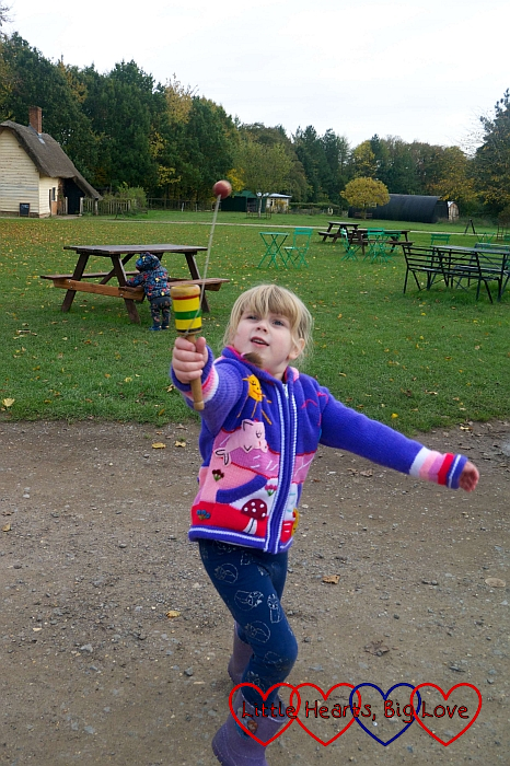 Sophie playing with a wooden cup and ball game on the village green