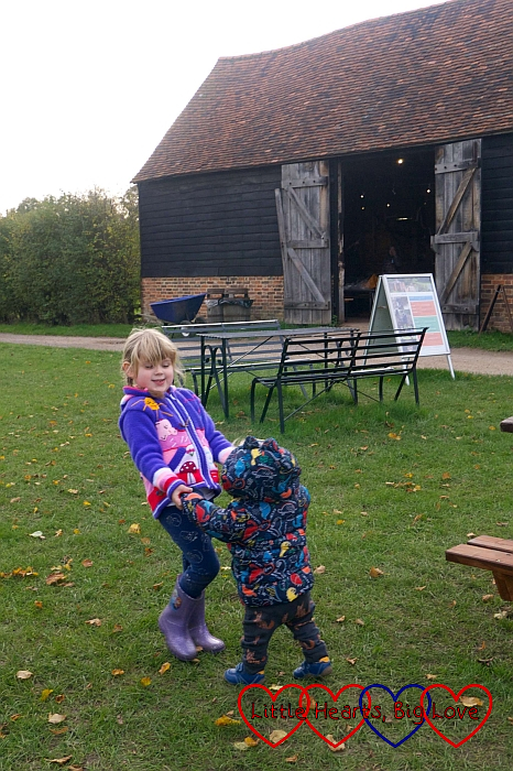 Sophie holding Thomas's hands and helping him walk across the village green