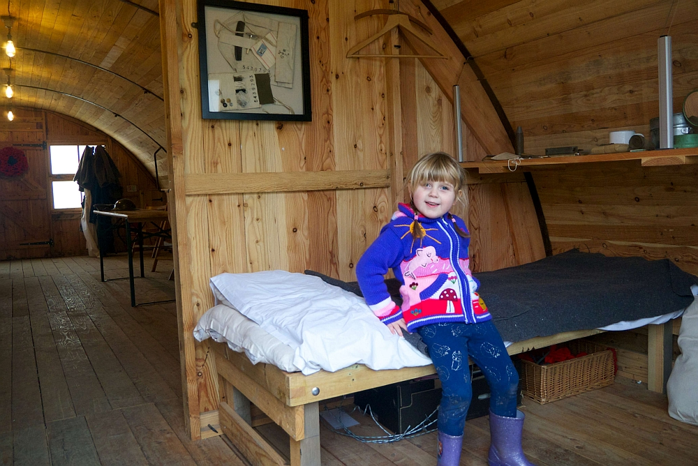 Sophie sitting on a wooden bed inside the WW1 Nissen Bow Hut