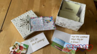A box of envelopes labelled for each month with notecards showing family time ideas