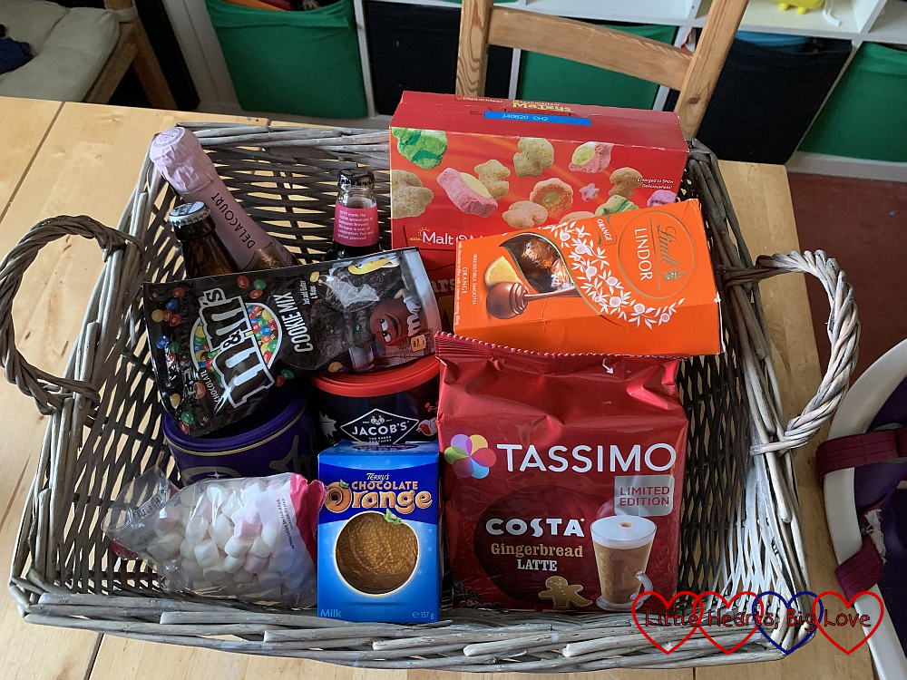 A hamper filled with coffee, chocolate, wine and some other food treats