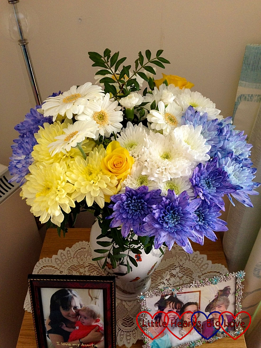 A vase full of yellow, white and blue flowers