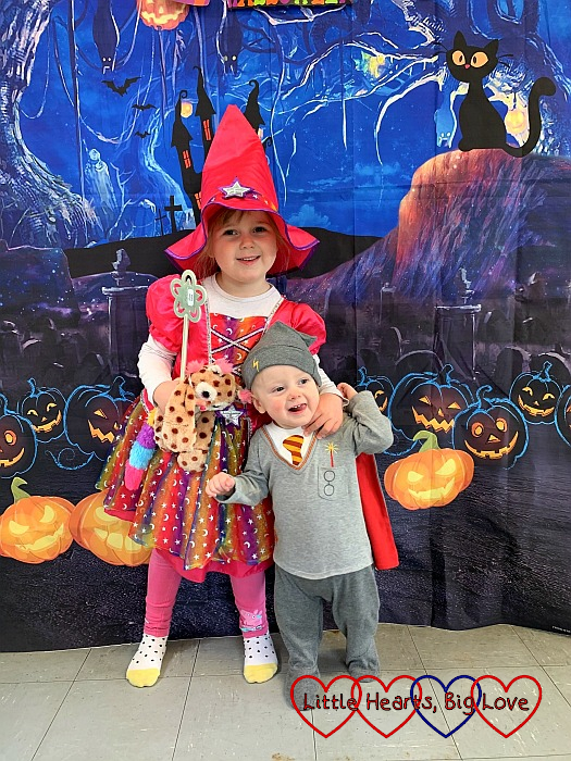 Sophie and Thomas dressed as a rainbow witch and Harry Potter in front of the Halloween selfie wall at Tiny Talk