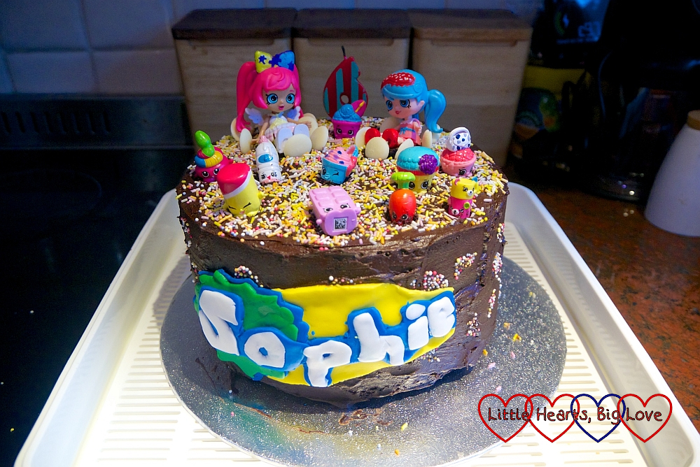 """Sophie's birthday cake - a chocolate cake with the word """"Sophie"""" in the style of the Shopkins logo in fondant on the side and sprinkles and Shopkins figures on the top"""