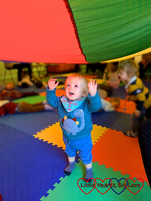 Thomas underneath the coloured parachute reaching up for it
