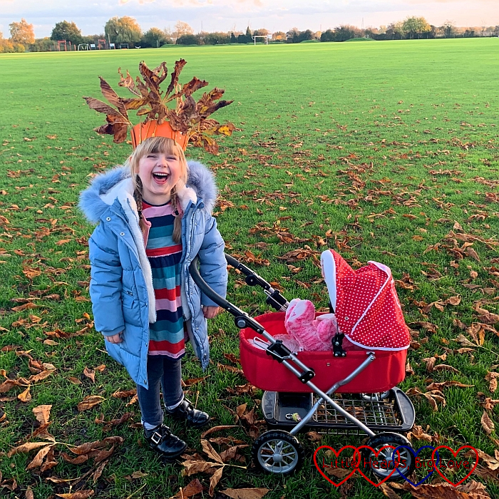 Sophie with her doll's pram, wearing an autumn crown made of leaves stuck to cardboard
