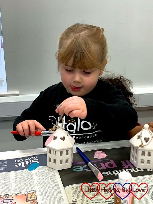 Sophie painting a ceramic lantern