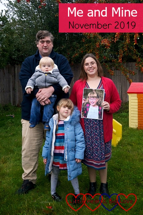 """Hubby holding Thomas, me holding a photo of Jessica and Sophie standing in front of us as we pose in the garden - """"Me and Mine - November 2019"""""""
