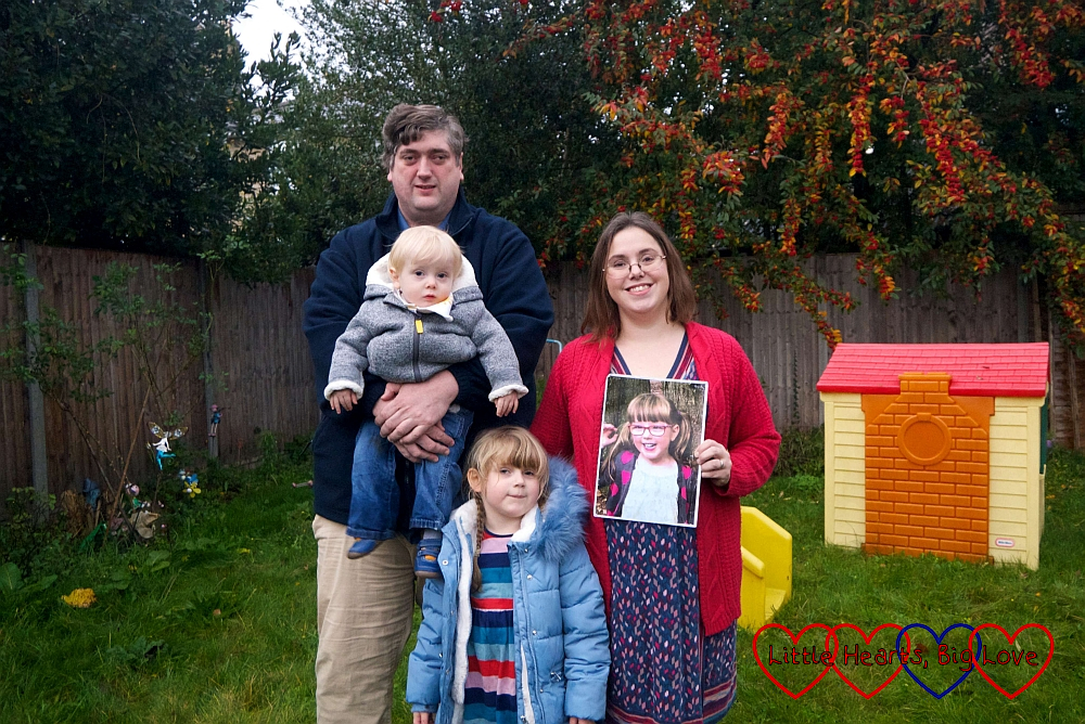 Hubby holding Thomas, me holding a photo of Jessica and Sophie standing in front of us as we pose in the garden