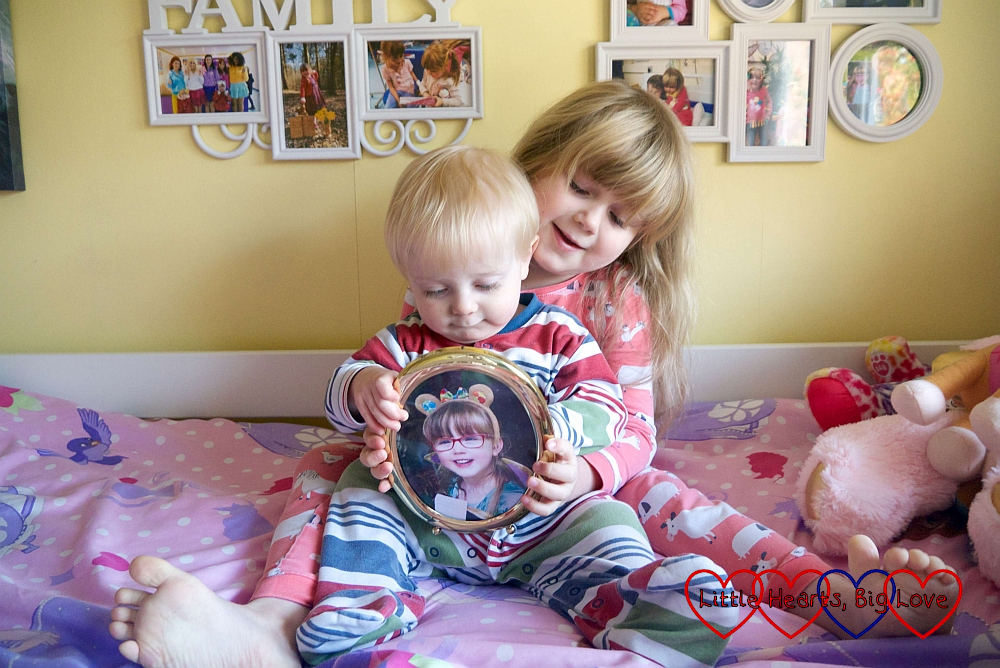 Sophie sitting on her bed with Thomas on her lap, holding a photo of Jessica