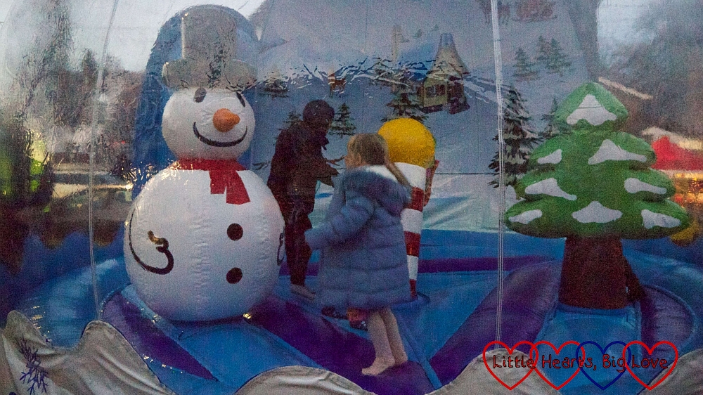 Sophie bouncing around a Christmas tree and snowman inside the inflatable snow globe