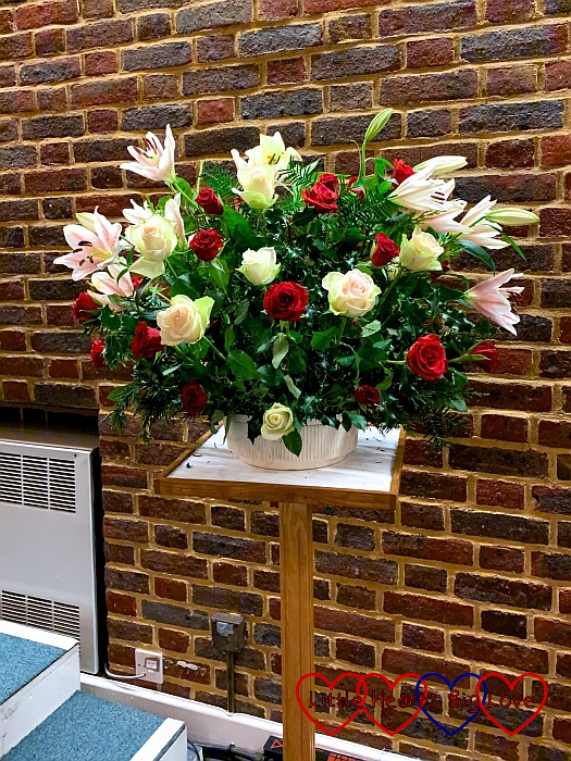 My flower arrangement at church with lilies, white and red roses, holly and fir