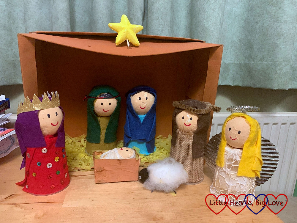 A shoebox nativity with models of a king, Mary and Joseph, a shepherd, an angel, a sheep and baby Jesus in a manger all made from cups, polystyrene balls and cardboard.