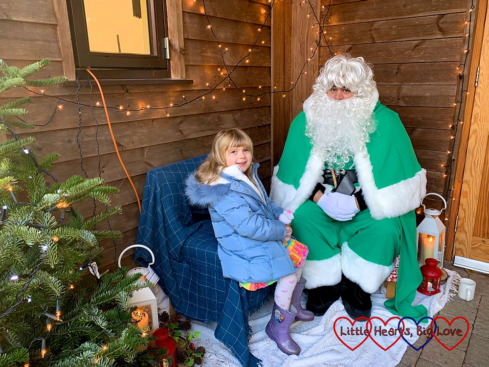 Sophie sitting with Father Christmas (dressed in green) outside the woodland hall at GreenAcres